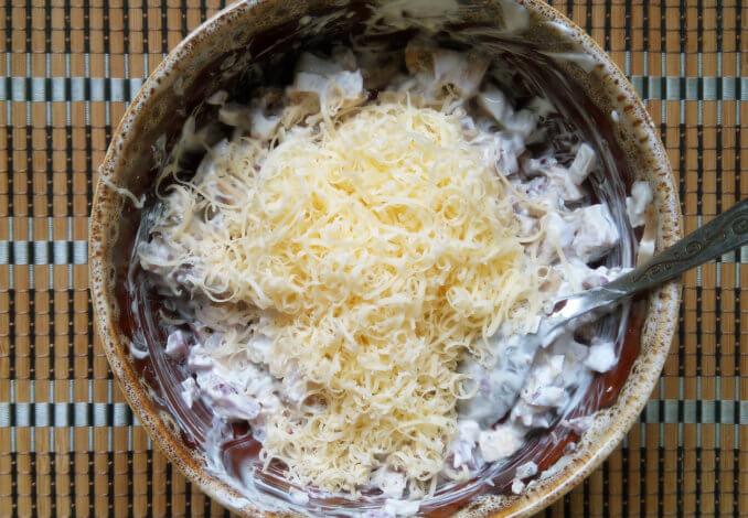 Хорошо смешиваем составляющие грибного жульена и вводим внутрь половину сыра